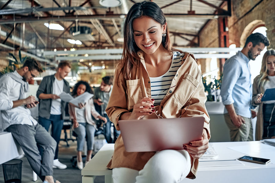 Business Insurance - Modern Business Woman Looking Over Documents in Her Open Office